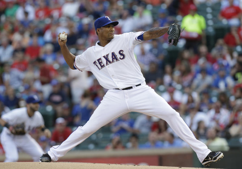 Texas Rangers starting pitcher Alexi Ogando throws during the first inning of a baseball game against the New York Yankees on Tuesday, July 23, 2013, in Arlington, Texas. (AP Photo/LM Otero)