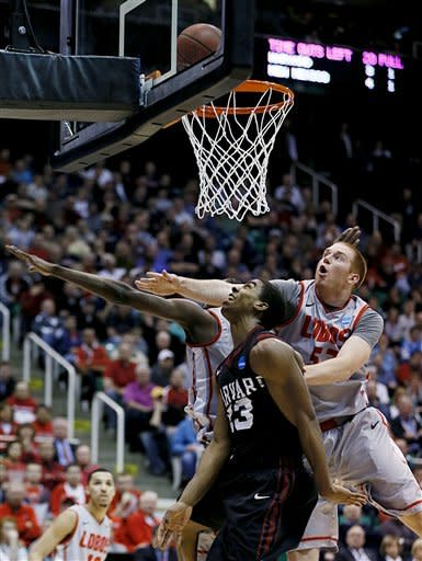 New Mexico's Alex Kirk, right, tries to block the shot of Harvard's Wesley Saunders in the first half during a second-round game in the NCAA college basketball tournament in Salt Lake City, Thursday, March 21, 2013. (AP Photo/George Frey)