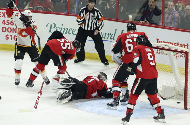 Calgary Flames center Sam Bennett, left, celebrates his goal as Ottawa Senators defenseman Erik Karlsson (65) goaltender Mike Condon (1) defenseman Ben Harpur (67) and right wing Bobby Ryan (9) watch the puck in the net during the first period of an NHL hockey game in Ottawa, Friday, March 9 2018. (Fred Chartrand/The Canadian Press via AP)
