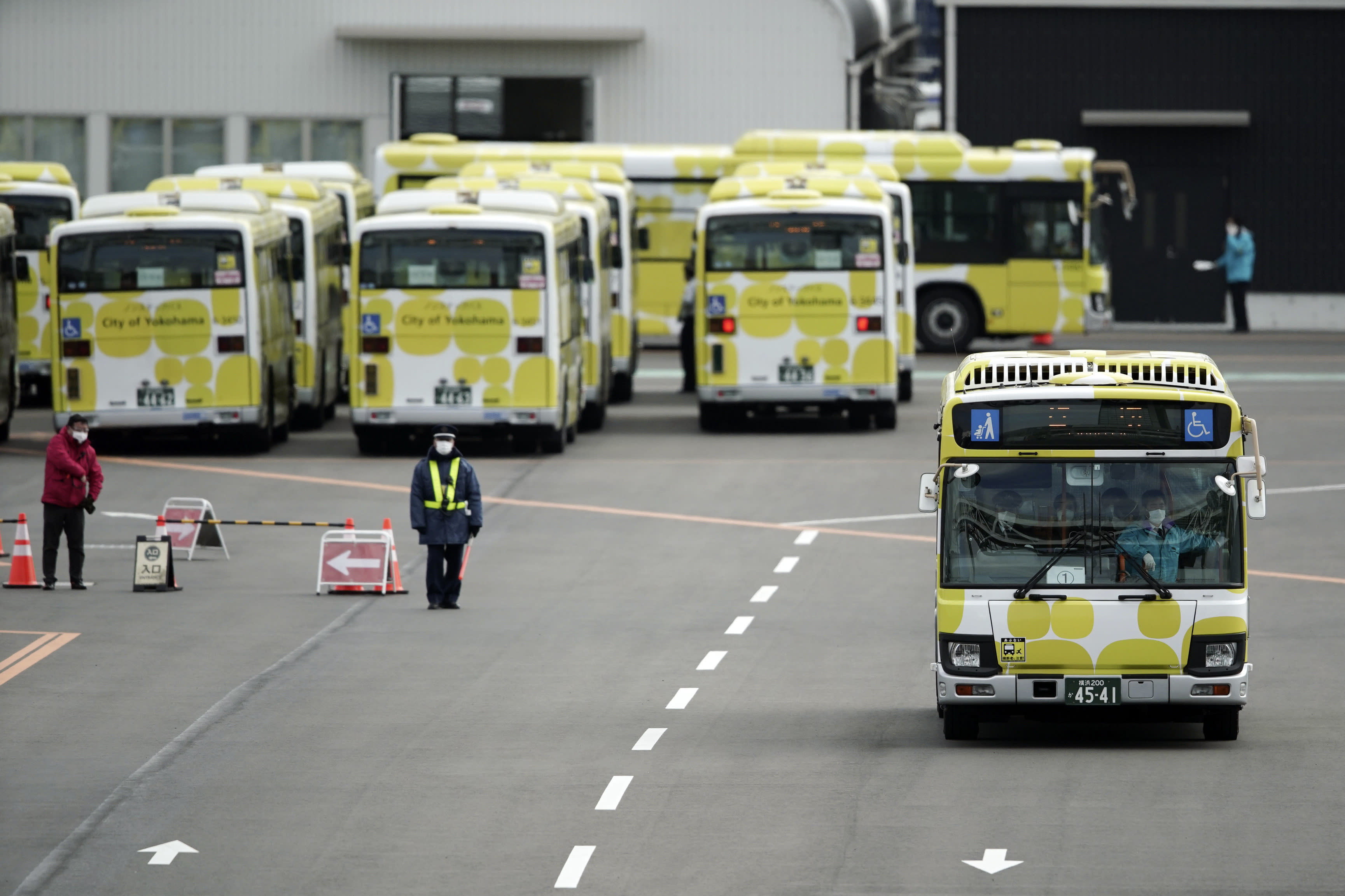 Buses carrying the passengers from the quarantined Diamond Princess cruise ship leave a port in Yokohama, near Tokyo, Wednesday, Feb. 19, 2020. Passengers tested negative for COVID-19 started disembarking Wednesday. (AP Photo/Eugene Hoshiko)