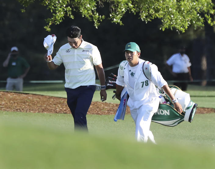 Hideki Matsuyama, of Japan, tips his cap as he walks to the 18th green with caddie Shota Hayafuji at the Masters golf tournament in Augusta, Ga., Sunday, April 11, 2021. A decade after Matsuyama made a sterling debut as the best amateur at Augusta National, he claimed the ultimate trophy with a victory in the Masters. (Curtis Compton/Atlanta Journal-Constitution via AP)