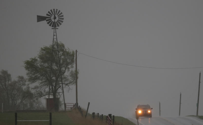 A vehicle tops a hill along U.S. Route 56 as a severe thunderstorm moves through the area near Baldwin City, Kan., Sunday, April 27, 2014. Severe storms are expected in the area most of the day. (AP Photo/Orlin Wagner)