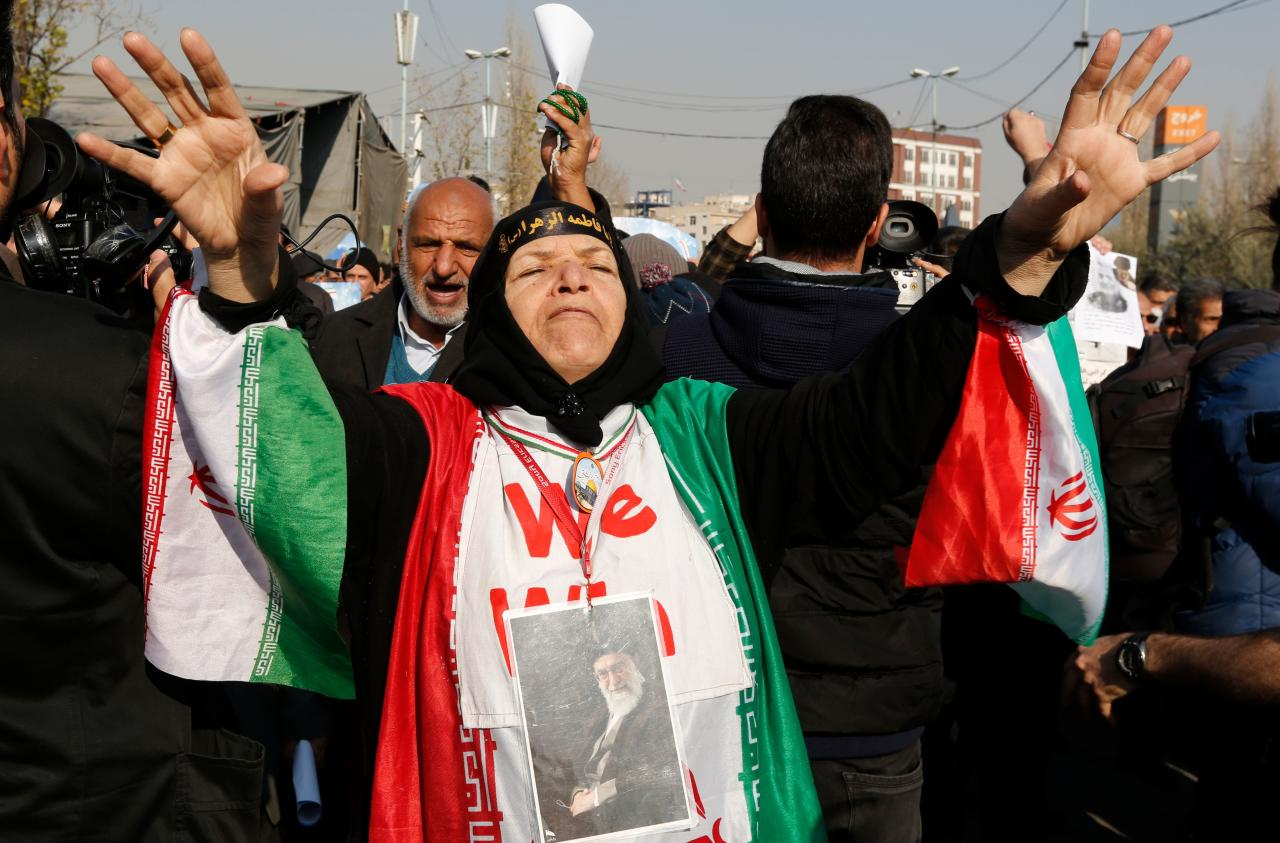 <p>An Iranian woman wearing a portrait of Supreme leader Ayatollah Ali Khamenei around her neck and the colours of the national flag shouts slogans during a pro-government march held after the weekly Friday prayers in central Tehran on Jan. 5, 2018. (Photo: Atta Kenare/AFP/Getty Images) </p>
