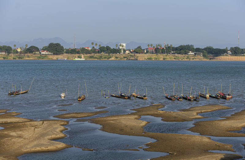 In this Wednesday, Dec. 4, 2019, photo,  fishing boats are moored in Mekong River, which has turned blue instead of its usual muddy color, in Nakhon Phanom province, northeastern Thailand. Experts say the aquamarine color the Mekong River has recently acquired may beguile tourists but it also indicates a problem caused by upstream dams. The water usually is a yellowish-brown shade due to the sediment it normally carries downstream. But lately it has been running clear, taking on a blue-green hue that is a reflection of the sky. The water levels have also become unusually low, exposing sandbanks in the middle of the river. (AP Photo/Chessadaporn Buasai)