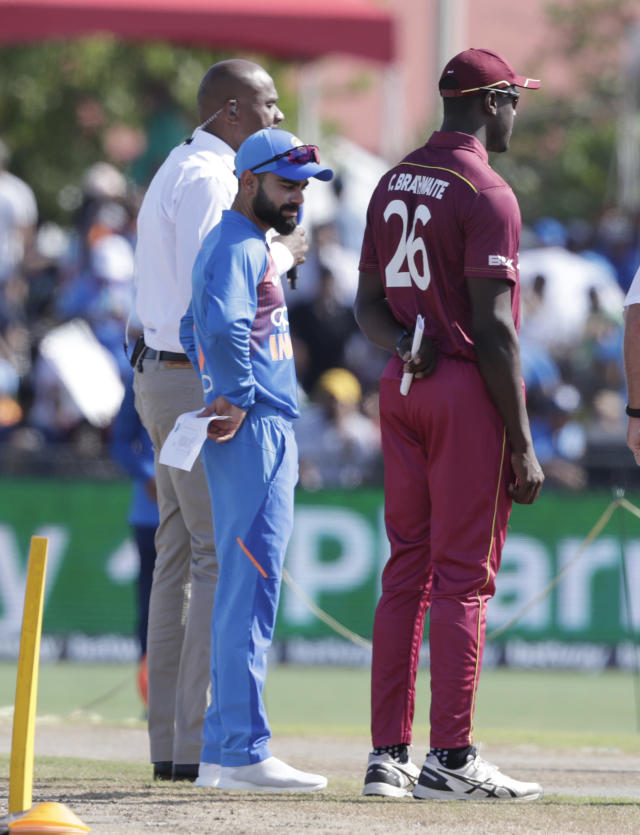 India captain Virat Kohli, left, and West Indies captain Carlos Brathwaite (26) stand on the field before the first Twenty20 international cricket match, Saturday, Aug. 3, 2019, in Lauderhill, Fla. (AP Photo/Lynne Sladky)