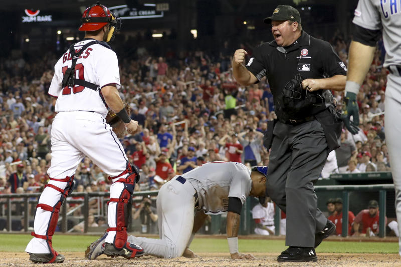 Umpire Sam Holbrook calls out Chicago Cubs' Addison Russell (27) after Washington Nationals catcher Yan Gomes (10) tagged him out after a passed ball to end the top of the fifth inning of a baseball game Saturday, May 18, 2019, in Washington. (AP Photo/Andrew Harnik)