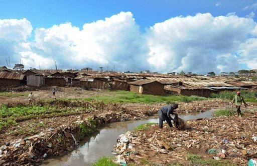 Two men rumage for discarded flip-flops and other rubber waste among trash near Africa's largest slum Kibera