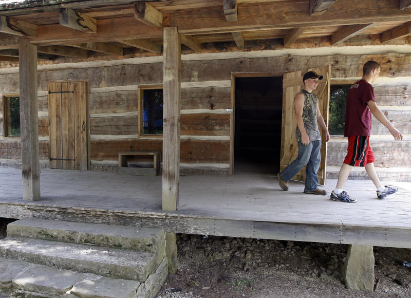 FILE - In a Saturday, June 9, 2012 file photo, Jordan Stamper, right, and James Ball look over a cabin that marks the site of key events in the Hatfield-McCoy feud, warring families known for violent clashes during the Civil War era, near Matewan, W.V. Artifacts unearthed last year during filming of a new National Geographic Channel show appear to pinpoint the location of an 1888 ambush on Randolph McCoy's cabin by the Hatfield clan in the woods of eastern Kentucky. Excavators found bullets believed to have been fired by the McCoys in self-defense, along with fragments of windows and ceramic from the family's cabin. Property owner Bob Scott, a Hatfield descendant, plans to capitalize on the historic 70-acre site in eastern Pike County near the West Virginia line. The options include a housing development featuring horseback and ATV trails, he said. (AP Photo/James Crisp, File)
