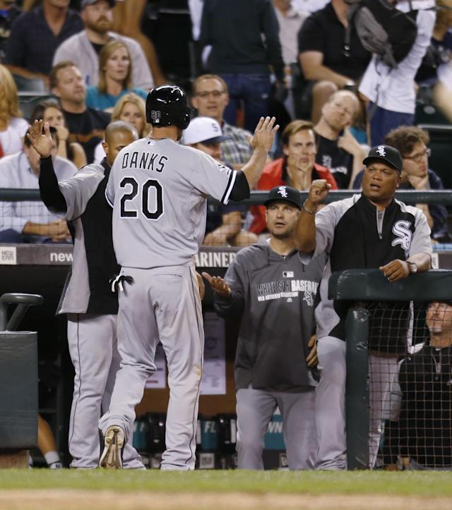Chicago White Sox's Jordan Danks is greeted at the dugout after scoring against the Seattle Mariners during the 10th inning of a baseball game in Seattle on Saturday, Aug. 9, 2014. The White Sox won 2-1. (AP Photo/John Froschauer)