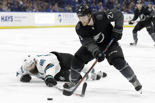Tampa Bay Lightning center Brayden Point (21) gets around a stick check by San Jose Sharks defenseman Brent Burns (88) during the second period of an NHL hockey game Saturday, Dec. 7, 2019, in Tampa, Fla. (AP Photo/Chris O'Meara)