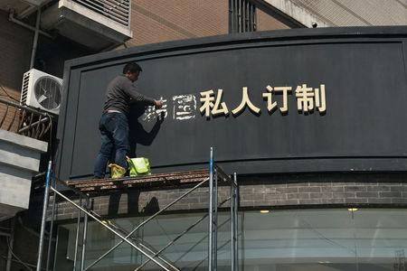 A worker removes part of a sign that consists of the Chinese characters that collectively read South Korea, at a shop in Shanghai,