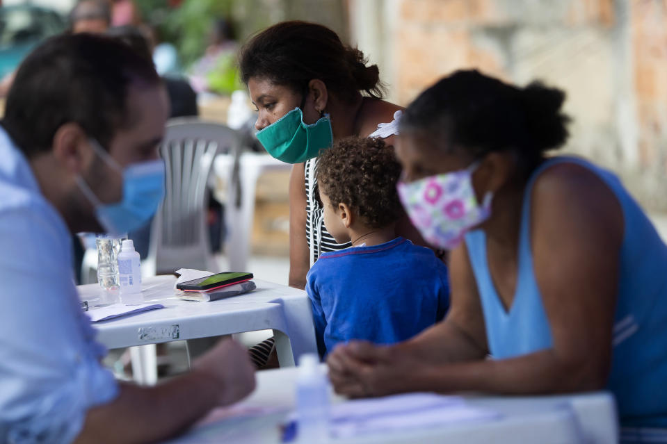 Residents receive medical attention during a campaign organized by doctors and volunteers amid the new coronavirus pandemic in the Chapadao favela in Rio de Janeiro, Brazil, Saturday, Oct. 17, 2020. The residents received health assistance, protective face masks, legal advise and food as part of the campaign. (AP Photo/Bruna Prado)