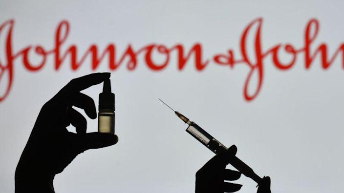 Silhouette of a man holding a medical syringe and a vial seen displayed in front of the Johnson and Johnson logo on a screen