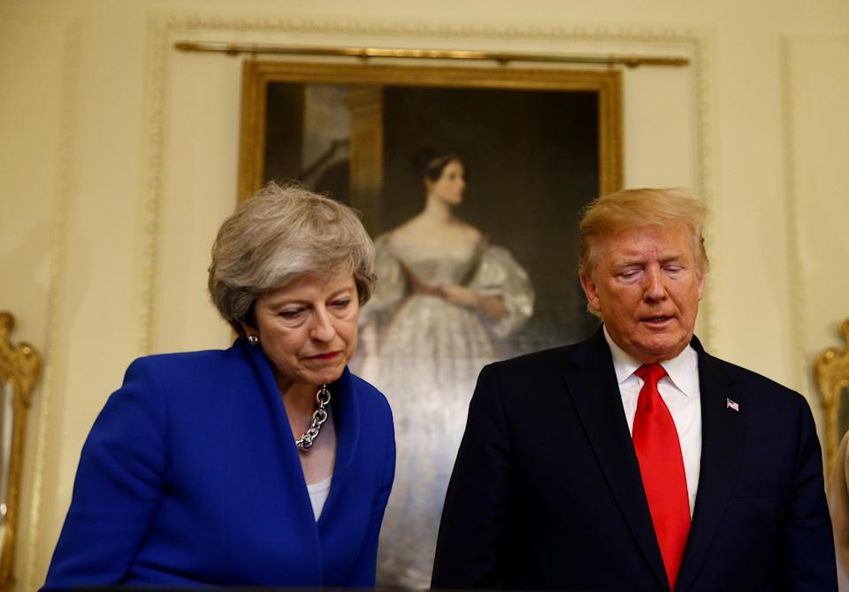 Prime Minister Theresa May with US President Donald Trump view a historical document in Downing Street, London, on the second day of his state visit to the UK.
