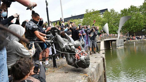 PHOTO: Protesters throw a statue of slave trader Edward Colston into Bristol harbour, during a Black Lives Matter protest rally, in Bristol, England, June 7, 2020, in response to the recent death of George Floyd. (Ben Birchall/PA via AP)
