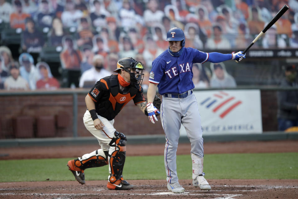 San Francisco Giants catcher Tyler Heineman, left, tags out his brother Texas Rangers' Scott Heineman after a foul tip during the second inning of a baseball game Saturday, Aug. 1, 2020, in San Francisco. (AP Photo/Ben Margot)