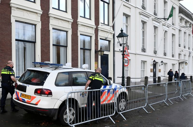 Police officers stand near the Embassy of Saudi Arabia after unidentified assailants sprayed it with gunfire, in The Hague