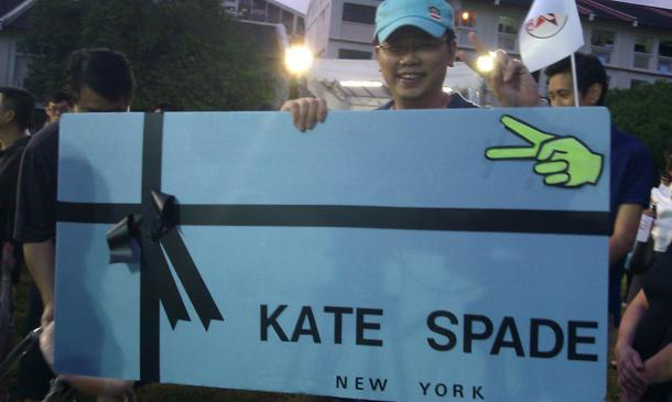 Reno Tan, a Marine Parade resident, made this Kate Spade board to make a statement at the rallies he attended. Here, he poses with it at an SPP rally. (Yahoo! photo / Jeanette Tan)