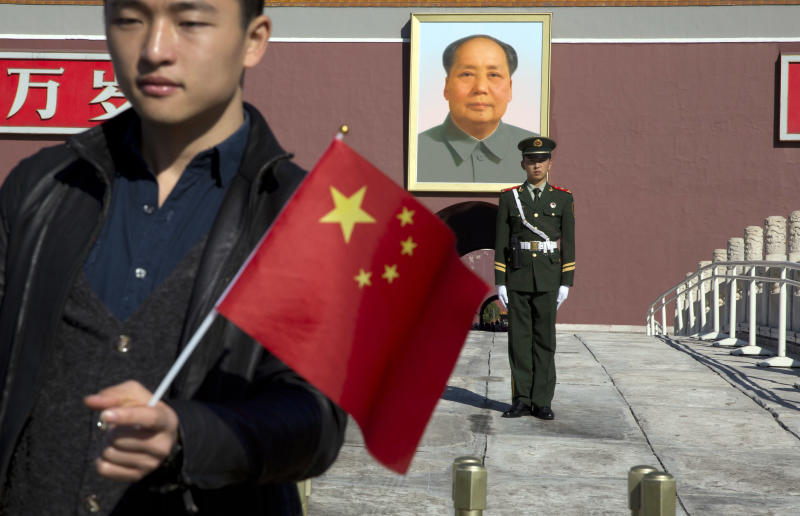 A tourist holds up a Chinese flag as he poses for photos near a Chinese paramilitary policeman on duty in front of former Chinese leader Mao Zedong's portrait on Tiananmen Gate, close to the site of an incident Monday where a car plowed through a crowd before it crashed and burned in Beijing, China, Tuesday, Oct. 29, 2013. Police investigating the apparent car attack at Beijing's Forbidden City searched Tuesday for information on two ethnic Uighur minority suspects, a hotel employee said, a day after the incident which killed five people and injured 38.(AP Photo/Ng Han Guan)