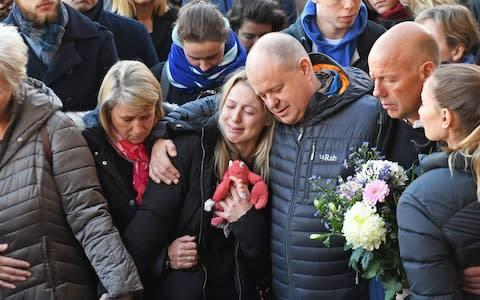 <span>Leanne O'Brien, the girlfriend of Jack Merritt, is comforted by family members during a vigil at The Guildhall in Cambridge </span> <span>Credit: SWNS </span>