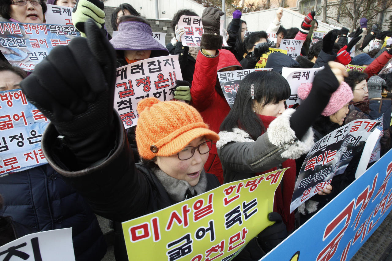 "South Korean house wives shout slogans during a rally denouncing North Korea's rocket launch in Seoul, South Korea, Thursday, Dec. 13, 2012. North Korea successfully fired a long-range rocket on Wednesday, defying international warnings as the regime of Kim Jong Un took a big step forward in its quest to develop a nuclear missile. The letters read "" Denounce North Korea's rocket launch and beat Kim Joung Un"". (AP Photo/Ahn Young-joon)"