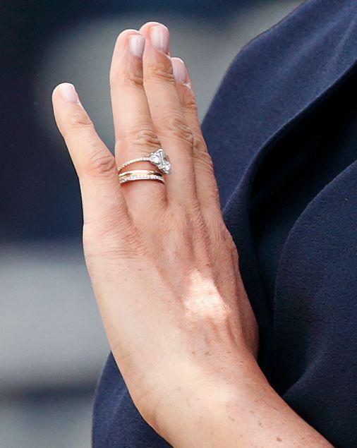 """<p>The royal made her first public appearance after the birth of her son at the 2019 Trooping of the Colour ceremony, and fans were quick to notice something different about Markle's left finger. The Duchess of Sussex debuted a <a href=""""https://www.townandcountrymag.com/style/jewelry-and-watches/a28157762/meghan-markle-redesigned-engagement-ring-photos/"""" rel=""""nofollow noopener"""" target=""""_blank"""" data-ylk=""""slk:revamped engagement ring"""" class=""""link rapid-noclick-resp"""">revamped engagement ring</a>—replacing the original gold band with a thinner band of pavé diamonds—as well as a new diamond eternity band on her stack. </p>"""