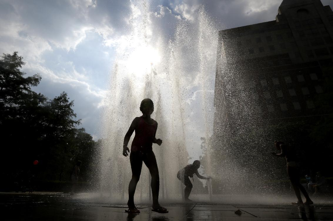 Children play on a fountain at Pier A Park during a heat wave, Wednesday, July 17, 2013, in Hoboken, N.J. (AP Photo/Julio Cortez)