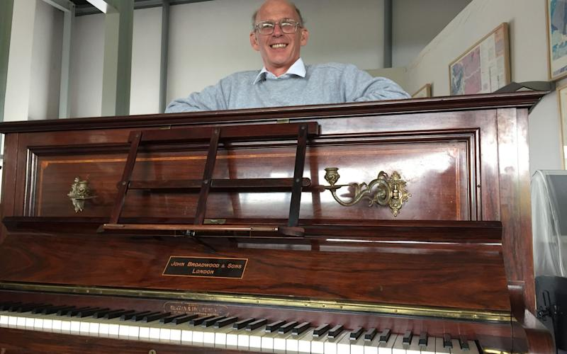 Tuner Martin Backhouse at Ludlow Museum with the piano in which he found the £500,000 hoard - Credit: PA