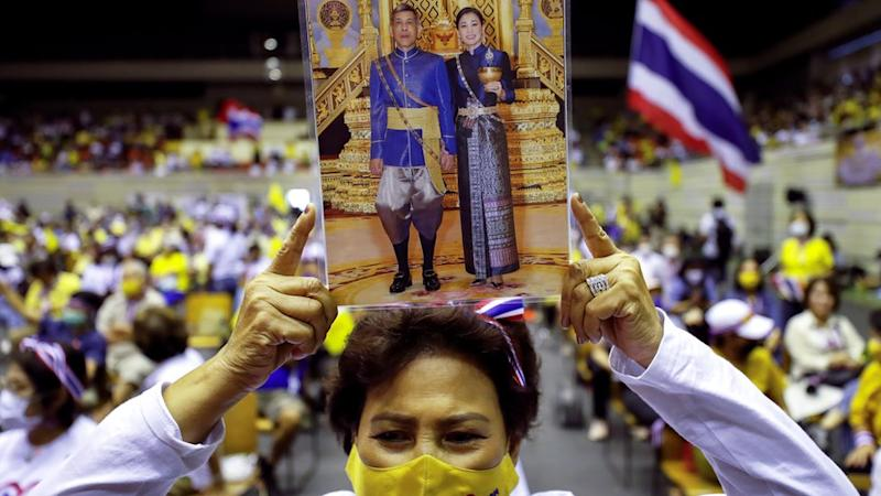 """A person holds a picture of Thai King Maha Vajiralongkorn with Queen Suthida as members of Thai right-wing group """"Thai Pakdee"""" (Loyal Thai) attend a rally in support of the government and the monarchy and in opposition to the recent anti-government protests, in Bangkok, Thailand August 30, 2020"""