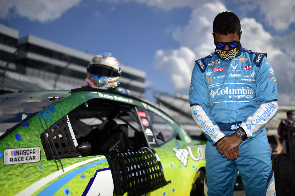 Bubba Wallace stands with his head bowed next to his car during the pre-race ceremonies prior to the NASCAR Cup Series Drydene 311 at Dover International Speedway.