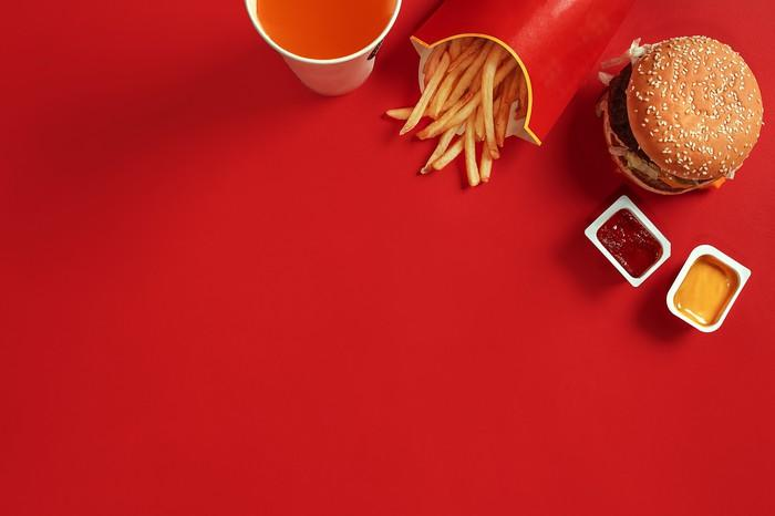 A red table set with a hamburger, fries, dipping sauces, and a drink