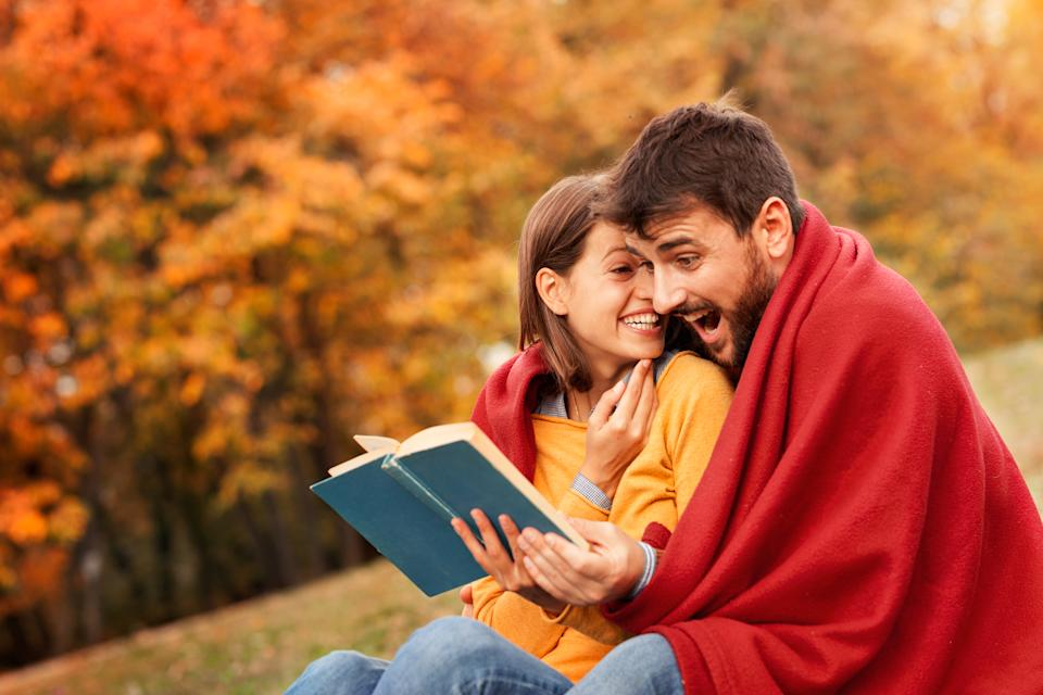 Loving couple wrapped with a blanket reading very diverting book