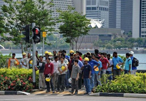 Construction workers wait to cross a street in Singapore on June 10, 2011. Maligned by some Singaporeans for supposedly stealing jobs and causing overcrowding, foreigners holding work permits numbered more than 870,000 at the end of 2010 out of Singapore's total population of 5.1 million