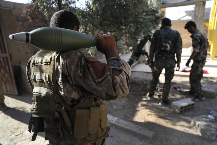 FILE - In this July 27, 2017 file photo, U.S.-backed Syrian Democratic Forces fighters prepare to fire a mortar shell, at one of the front lines, in Raqqa, northeast Syria. Syrian activists said Friday, Dec. 14, 2018 that U.S.-backed, Kurdish-led fighters have captured the last town held by the Islamic State group, in the militants' single remaining enclave in eastern Syria. (AP Photo/Hussein Malla, File)