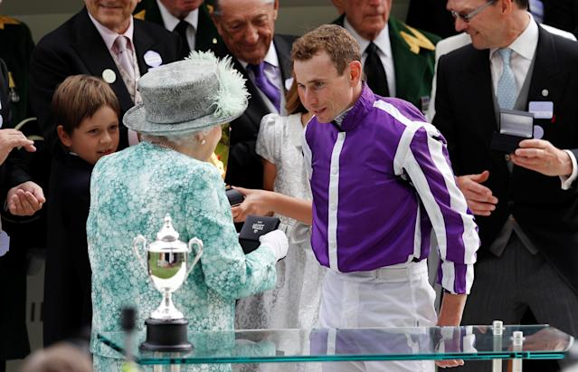 Horse Racing - Royal Ascot - Ascot Racecourse, Ascot, Britain - June 23, 2018 Britain's Queen Elizabeth presents a trophy for the 4.20 Diamond Jubilee Stakes to Ryan Moore, who rode the winner Merchant Navy REUTERS/Peter Nicholls