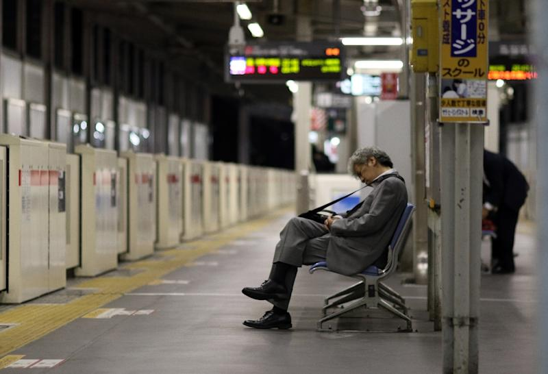 """Japan's """"salaryman"""" is popularly considered to work long hours, before drinking with the boss and taking the last train home (AFP Photo/YOSHIKAZU TSUNO)"""