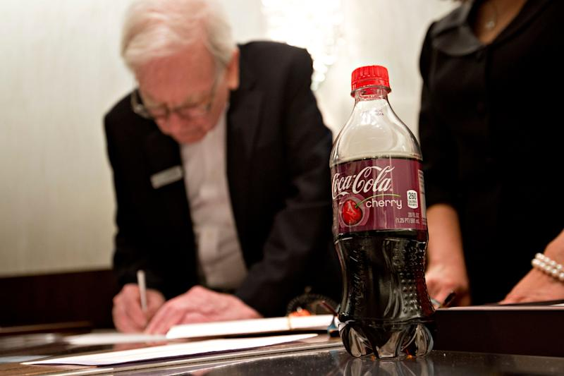 A Cherry Coca-Cola sits on the counter as Warren Buffett, chairman of Berkshire Hathaway Inc., sells jewelry at Borsheim's Jewelry on the sidelines of the Berkshire Hathaway shareholders meeting in Omaha, Nebraska, U.S., on Sunday, May 4, 2014. Warren Buffett whose Berkshire Hathaway Inc. joined 3G Capital last year in a $23.3 billion takeover of ketchup maker HJ Heinz Co., said yesterday he'd welcome more deals with the buyout firm. Photographer: Daniel Acker/Bloomberg via Getty Images