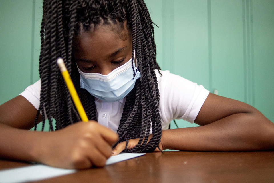 """Sixth-grader Adriana Campbell, 11, jots down her name as she starts to work on her first assignment during the first day of school on Wednesday, Aug. 4, 2021 at Freeman Elementary School in Flint, Mich. """"I'm excited to learn. I love math,"""" she said. """"When I woke up today, I couldn't wait to get to school. I can't wait to make new friends."""" (Jake May/The Flint Journal via AP)"""