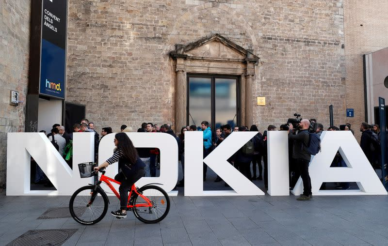 FILE PHOTO: A cyclist rides past a Nokia logo during the Mobile World Congress in Barcelona