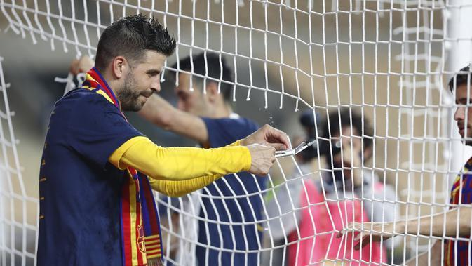 Bek Barcelona, Gerard Pique memotong sebagian jala gawang saat mereka merayakan kemenangan atas Athletic Bilbao pada final Copa del Rey Spanyol 2021 di stadion La Cartuja di Seville, Spanyol, Minggu (18/4/2021). Barcelona menang atas Athletic Bilbao 4-0. (AP Photo / Angel Fernandez)