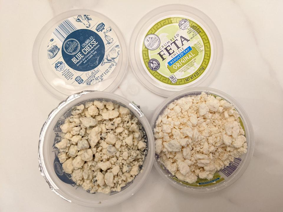 Aldi blue cheese and feta crumbles in their original plastic containers on a white countertop