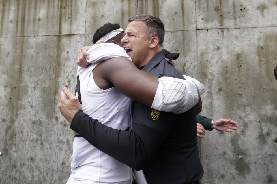 Oregon head coach Mario Christobal, right, embraces La'Mar Winston Jr. after the team beat Washington in an NCAA college football game Saturday, Oct. 19, 2019, in Seattle. Oregon won 35-31. (AP Photo/Elaine Thompson)