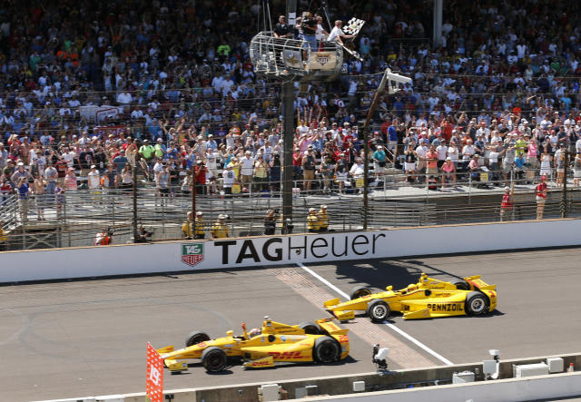 FILE - In this May 25, 2014, file photo, Ryan Hunter-Reay celebrates after crossing the finish line, taking the checkered flag in front of Helio Castroneves, of Brazil, to win the 98th running of the Indianapolis 500 IndyCar auto race at the Indianapolis Motor Speedway in Indianapolis. The Associated Press has updated its survey of living Indianapolis 500 winners and their pick as the greatest race in the long history of the event. There are six races that received multiple votes, topped by Al Unser Jr.'s victory over Scott Goodyear in 1992 — the closest Indy 500 in history. The others are Emerson Fittipaldi's win in 1989; Sam Hornish Junior's win in 2006; the 1982 battle between Rick Mears and Gordon Johncock; the 2011 race won by the late Dan Wheldon; and the 2014 thriller won by Hunter-Reay. (AP Photo/Dave Parker, File)