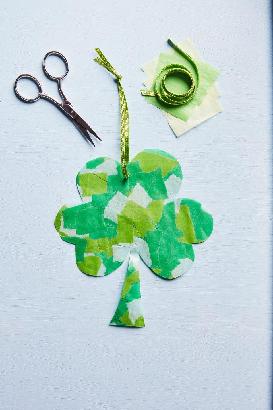 """<p>This sweet four-leaf clover ornament will look equally cute hanging from a magnet on the fridge or on the front door. Make it as small or large as desired.<strong><br></strong></p><p><strong>To make:</strong> Tear light green, dark green, and white tissue paper into small pieces. Lay pieces in between self-sealing laminating pouches; seal. Cut out a four-leaf clover shape. Punch a small hole in the top of the clover with a small hole-punch. Thread ribbon through the hole and hang.</p><p><a class=""""link rapid-noclick-resp"""" href=""""https://www.amazon.com/Scotch-Self-Sealing-Laminating-LS854-25G-WM-LS854WC/dp/B00006HZ5F/ref=sr_1_3?tag=syn-yahoo-20&ascsubtag=%5Bartid%7C10050.g.4036%5Bsrc%7Cyahoo-us"""" rel=""""nofollow noopener"""" target=""""_blank"""" data-ylk=""""slk:SHOP LAMINATING SHEETS"""">SHOP LAMINATING SHEETS</a></p>"""