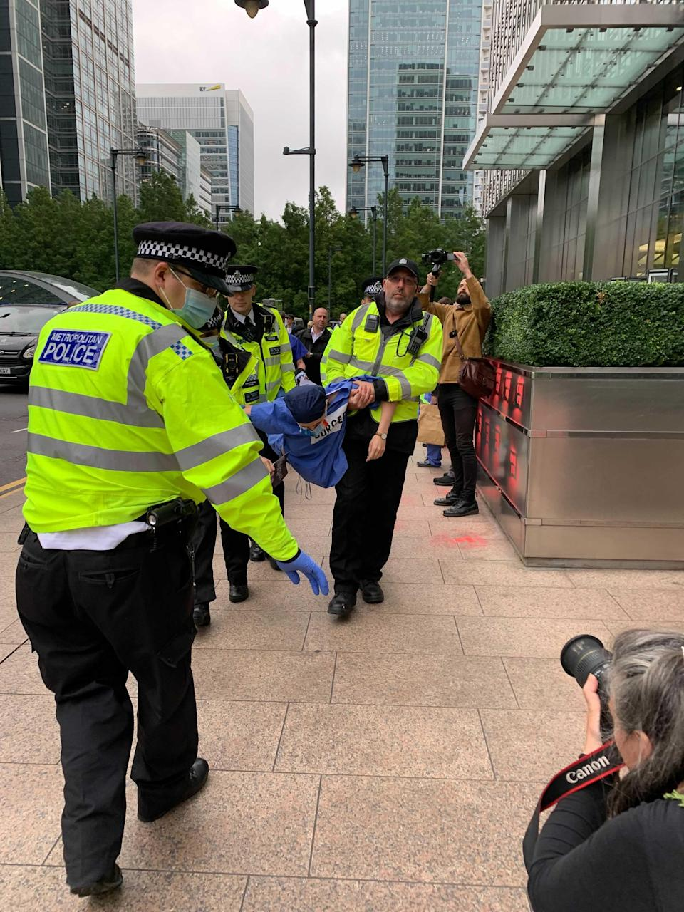 Police carry a protester away (The Independent)