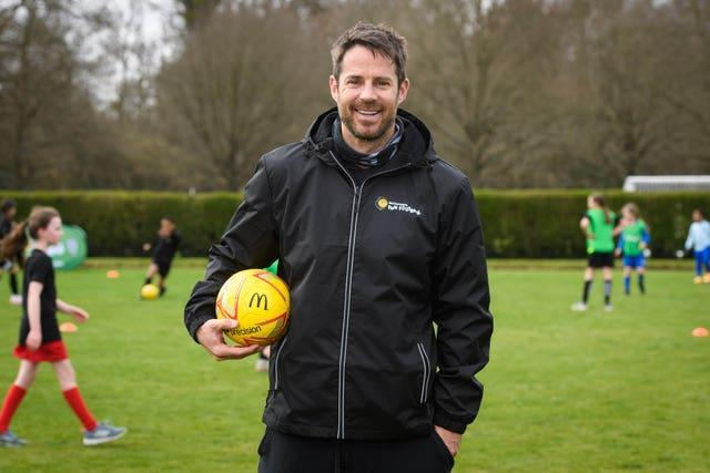 Jamie Redknapp holds a ball at a coaching session for children
