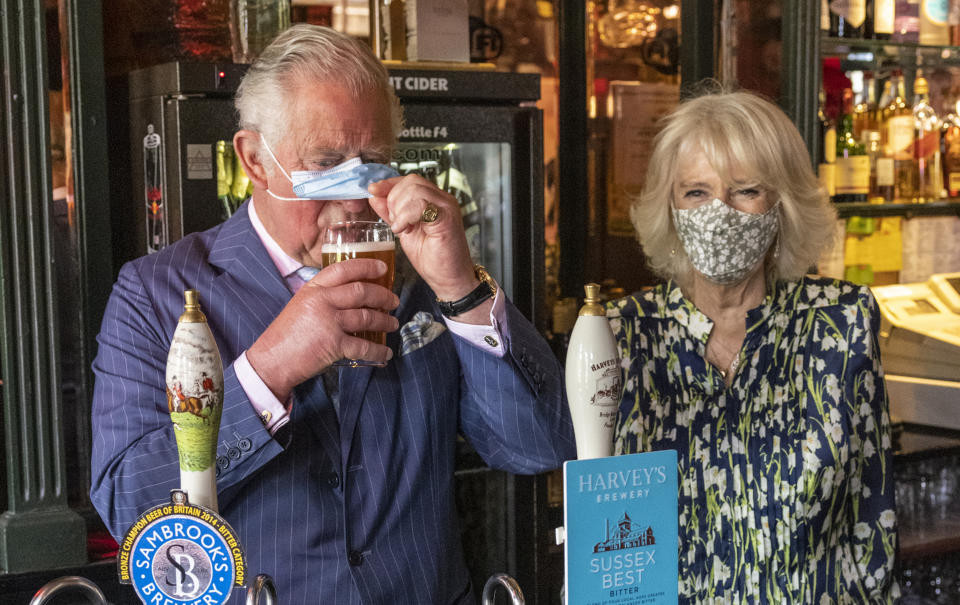 CLAPHAM, ENGLAND - MAY 27: Prince Charles, Prince of Wales adjusts his face mask to enable him to sip a pint that he pulled in a pub alongside Camilla, Duchess of Cornwall during a visit to Clapham Old Town on May 27, 2021 in Clapham, England. (Photo by Heathcliff O'Malley - WPA Pool/Getty Images)