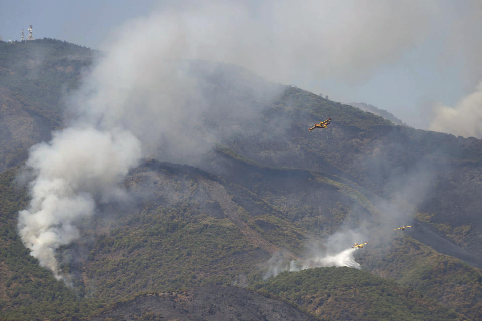 Hydroplanes operate on a wildfire in Estepona, in Malaga province, Spain, Saturday, Sept. 11, 2021. Soldiers were deployed in southeastern Spain Sunday to join the battle against a major wildfire that is burning for a fourth day, invigorated by a stray ember that has sparked a new hotspot. (Álex Zea/Europa Press via AP)