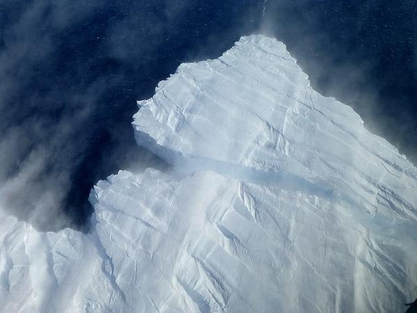 A nascent iceberg breaks off Pine Island Glacier's calving front. Icebergs in this area of the Amundsen Sea most often rise between 150 and 200 feet above the water surface. The image, taken from NASA's DC-8 on Nov. 4, 2012, also shows snow bei