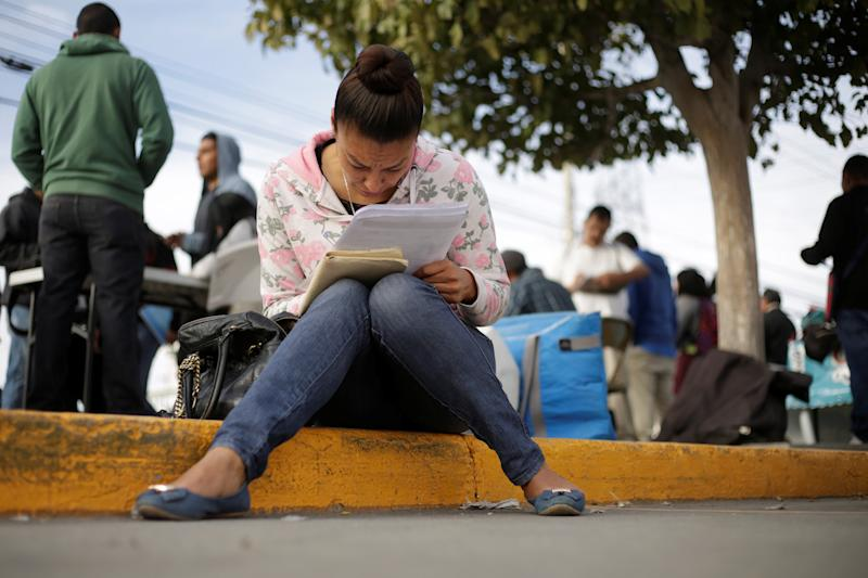Unemployed woman fills a job application at a parking lot  in Ciudad Juarez